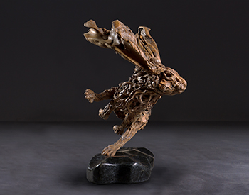 A hare takes a really tight turn Long dead driftwood on a stainless steel armature mounted on a solid marble base Slightly larger than life size