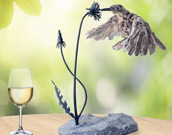 A Sunbird drinks nectar from a dandelion Long dead wood on a stainless steel armature Dandelion is stainless steel mounted on marble Edition of 8
