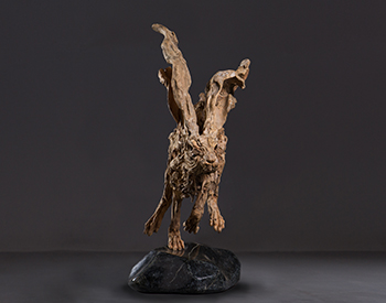 A hare lopes along Long dead driftwood on a stainless steel armature mounted on a solid marble base Slightly larger than life size