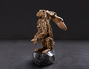 An introspective hare seeks affection Long dead driftwood on a stainless steel armature mounted on a solid marble base Slightly larger than life size
